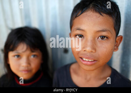 Poor vietnamese family living in a small barrack consists of scrap metal. Ethnic minority child. Young boy smiling.  Dalat. Vietnam. - Stock Photo