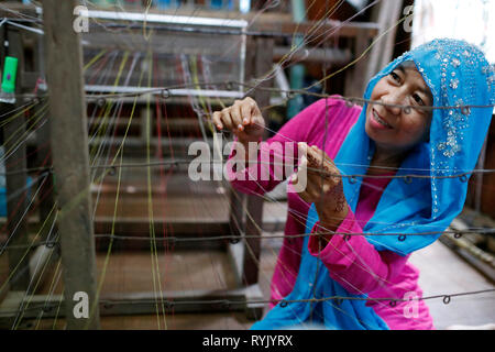Traditional hand loom.  Local muslim woman diligently weaving colourful scarves.  Chau Doc. Vietnam. - Stock Photo
