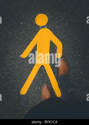 yellow pedestrian sign on pavement with feet - Stock Photo