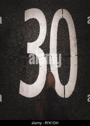30 zone marking on pavement with leather shoe - Stock Photo