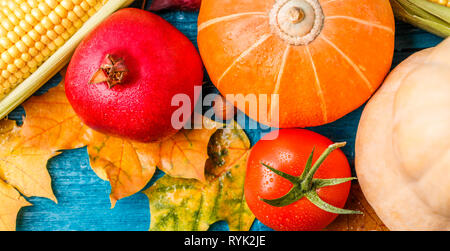 Image from above of autumn leaves, pumpkin, tomato, pomegranate, corn - Stock Photo