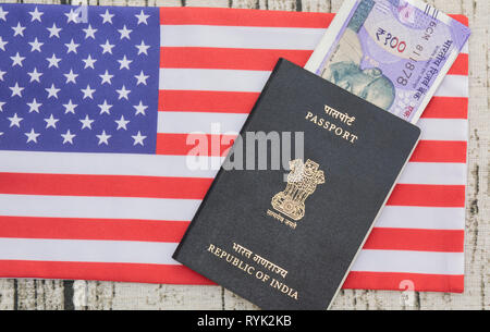 Indian passport with currency on USA or america's flag as a background - Stock Photo