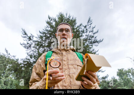 Photo of surprised man with compass - Stock Photo