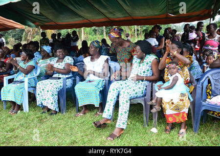 Anekro, ivory  coast- August 20, 2015: These women sitting under a tarpaulin applaud the authorities who arrive in their village - Stock Photo