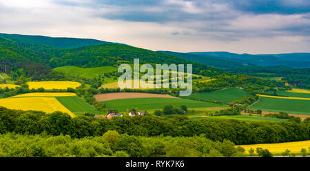 Lovely panoramic landscape view of the Werra Valley.  Green, yellow and brown cultivated fields surrounded by woodland and the North Hessian low... - Stock Photo