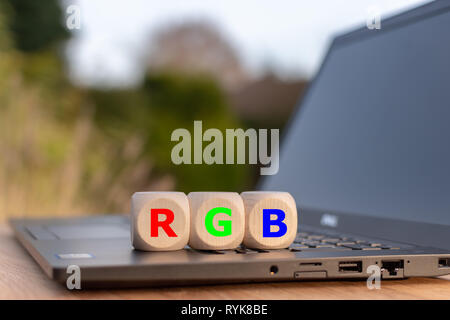 Symbol for the RGB color model. Dice placed on a notebook with the letters 'RGB' with corresponding colors. - Stock Photo