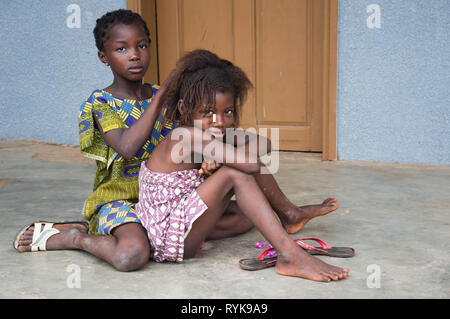 Anekro, ivory  coast- August 20, 2015: two girls sitting on the ground ; one braiding her friend and their gaze directed toward the camera - Stock Photo