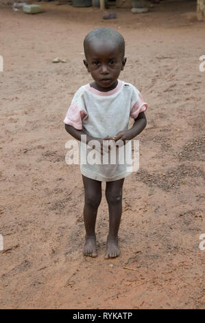 Anekro, ivory coast – August 20, 2015: Innocent African child, barefoot standing in their backyard setting the camera - Stock Photo