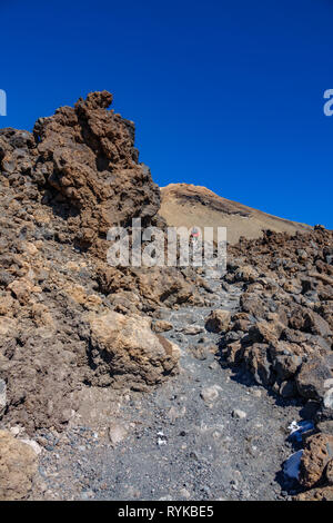 Trekking in the middle of lava fields ascending Teide volcano - Stock Photo
