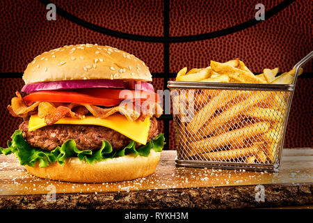 Cheeseburger with bacon and a basket of french fries. Basketball ball image in background. - Stock Photo