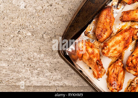 Barbecue chicken wings on an old cooking pan, concrete texture in background. Directly above. - Stock Photo