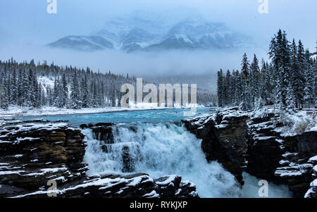 A fantastic image of waterfall, mountains, trees & fog while snowing, Athabasca Falls, Jasper, Canada. - Stock Photo