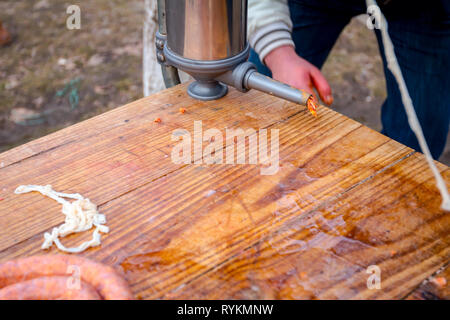 Butcher placing minced meat in machine for homemade sausages. - Stock Photo
