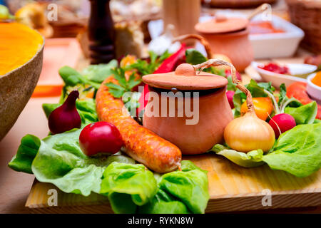 Roasted sausage with onion and clay pot is placed on a cutting board in traditional style. - Stock Photo