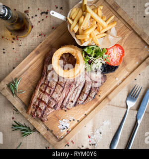 T Bone Steak from above with chips, tomato and mushroom on a wooden board and hessian with garnish - Stock Photo