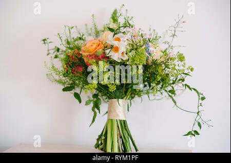 a pretty rustic wedding bouquet of flowers with pastel colours on a plain background - Stock Photo