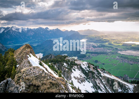 Scenic landscape overlooking snowy mountains and dramatic clouds. Sunlight rays falling on valley with lakes and small villages in Bavaria, Germany. - Stock Photo