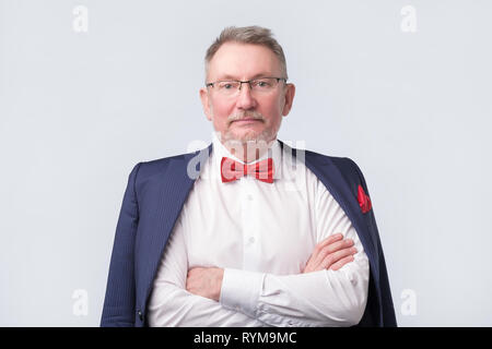 Senior man wearing eyeglasses aand blue suit smiling warmly and confident. - Stock Photo