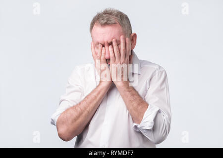 Senior man in white shirt covering his face with both hands - Stock Photo
