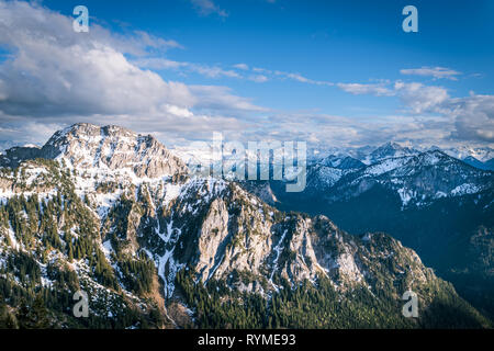 Scenic landscape in Alps overlooking the mountains with forest and snowy tops under dramatic sky in Bavaria, Germany. - Stock Photo