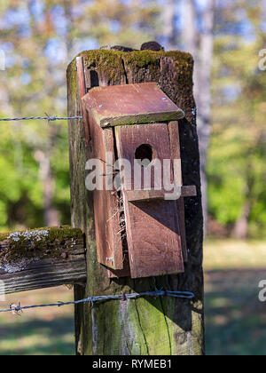 A wooden birdhouse on a mossy fence post. - Stock Photo
