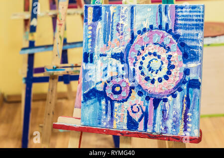 Painting on an easel in an art studio. Abstract painting of acrylic on canvas. - Stock Photo