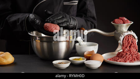 Cook in black gloves making meat balls of minced meat over metal bowl. Old grinder with raw beef and other ingredients on black kitchen table - Stock Photo