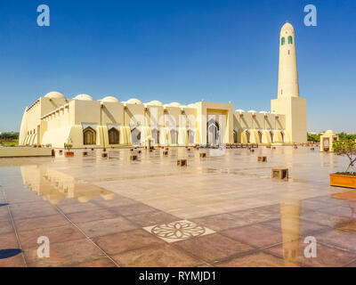 State Grand Mosque with a minaret reflecting on marble pavement outdoors. Doha mosque in Downtown, Qatar, Middle East, Arabian Peninsula. Morning - Stock Photo
