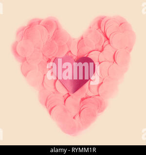 Colorful paper heart made of pink confetti with paper heart on beige background - Stock Photo