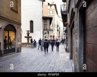 BERGAMO, ITALY - FEBRUARY 23, 2019: people walk on street via Gombito near fountain Fontana Del Gombito (Fontana di San Pancrazio) in Citta Alta (Uppe - Stock Photo