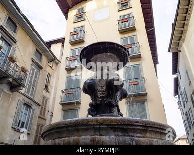 Travel to Italy - fountain Fontana Del Gombito (Fontana di San Pancrazio) and medieval apartment houses on street via Gombito in Citta Alta (Upper Tow - Stock Photo