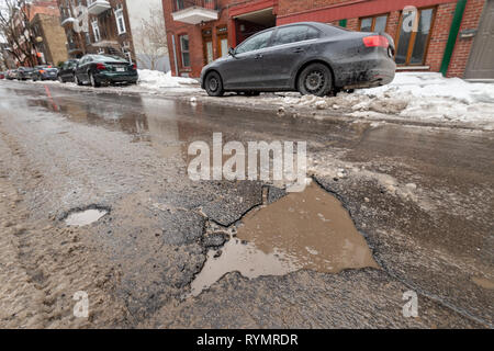 Montreal, CA - 13 March 2019: Large pothole in Montreal street, in Winter - Stock Photo