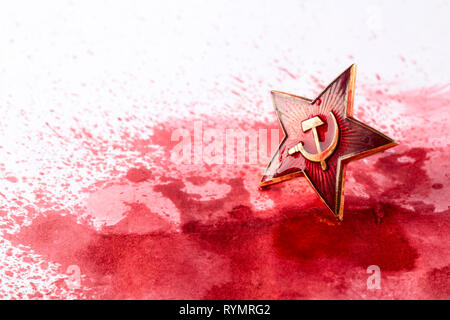 Soviet red star badge in blood - Stock Photo