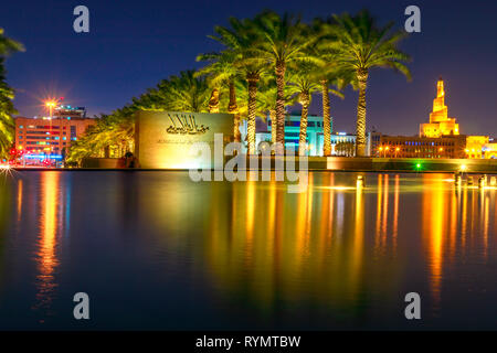 Doha, Qatar - February 20, 2019: Museum of Islamic Art sign and Fanar Islamic Cultural Center reflects in fountain water near Corniche promenade at - Stock Photo