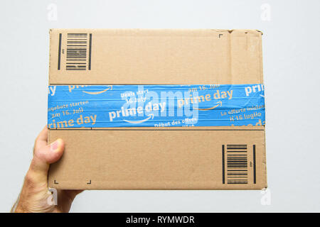 Paris, France - Jul 11, 2018: Man hand POV holding against white background sealed with special scotch tape of Amazon Prime parcel delivery - Stock Photo