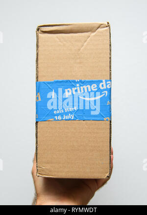 Paris, France - Jul 11, 2018: Man hand holding against white background sealed with special scotch tape of Amazon Prime parcel delivery - side view of the package - Stock Photo