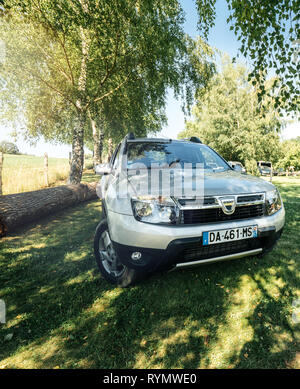 Vosges France - July 8 2018: French Romanian Dacia Duster SUV parked on the grass lawn in French mountains under a birch tree on a warm summer day - Stock Photo