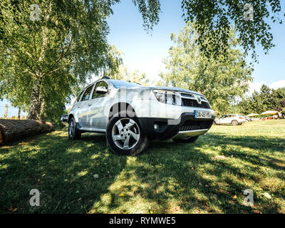 Vosges France - July 8 2018: Hero object of French Romanian Dacia Duster SUV parked on the grass lawn in French mountains under a birch tree with people having fun near a horse at farm rancho - Stock Photo