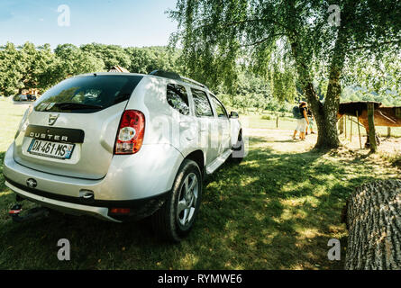 Vosges France - July 8 2018: French Romanian Dacia Duster SUV parked on the grass lawn in French mountains under a birch tree with people having young family admiring horse at rancho - Stock Photo