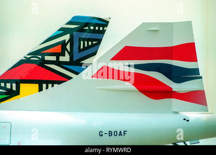 British Airways launch a new ethnic livery design of tail-fin art for their aircraft fleet. Pictured next to the traditional flag livery on a Concorde. - Stock Photo