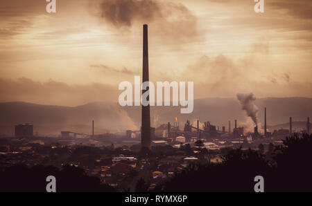 High view across industrial town to steel works and smoke stacks on atmospheric evening. Old industries, climate change and global warming concept - Stock Photo