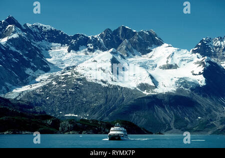 An excursion boat cruises past age-old snow-covered ice that slowly flows down rugged mountain valleys to Glacier Bay along the Inside Passage in southeast Alaska, USA. A ranger from Glacier Bay National Park and Preserve describes the awesome Alaskan terrain and wildlife seen on day-long tours that embarked from Bartlett Cove during the summer months. Besides icebergs and calving glaciers, passengers spot many seabirds and sea lions and may glimpse grizzly and black bears, moose, wolves and even mountain goats during the 130-mile (209-kilometer) water adventure in The Last Frontier. - Stock Photo