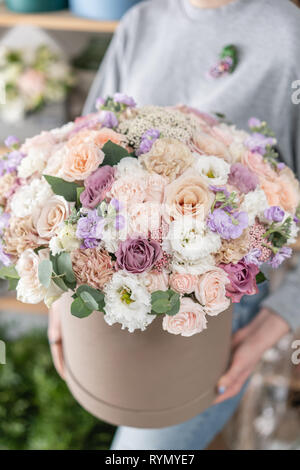 beautiful fresh cut bouquet of mixed flowers in woman hand. the work of the florist at a flower shop. - Stock Photo