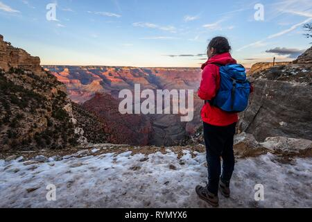 Young woman looking into the gorge of the Grand Canyon, view from the Bright Angel Trail, eroded rock landscape, South Rim - Stock Photo