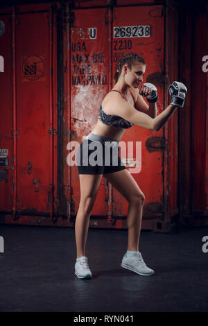 Beautiful athletic girl with boxing gloves posing at the garage background. - Stock Photo