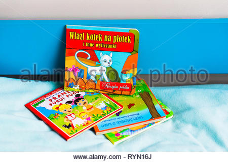 Poznan, Poland - November 18, 2018: Colorful child book about cat on a blue bed. - Stock Photo