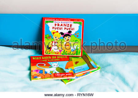 Poznan, Poland - November 18, 2018: Polish colorful book about laundry on a bed. - Stock Photo