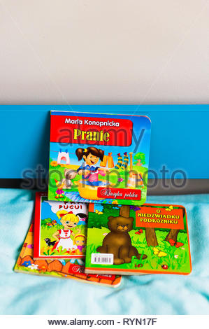 Poznan, Poland - November 18, 2018: Colorful child book about laundry on a blue bed. - Stock Photo