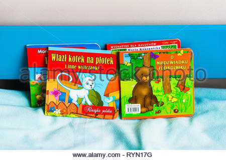 Poznan, Poland - November 18, 2018: Colorful Polish books on a blue bed with soft sheet. - Stock Photo