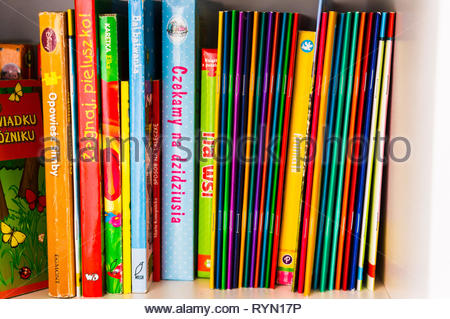 Poznan, Poland - November 18, 2018: Row of colorful Polish child books on a shelf. - Stock Photo